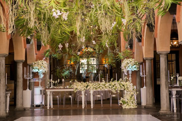 Greek Wedding Hanging Orchid Ceiling, Orchid Roof, suspended Orchid Ceiling with white orchid mass arrangements. White floral runners, white roses, white orchids. Green and white wedding. Hanging flowers wedding.