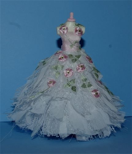 Rags to Riches. raggy lace and chiffon Bridal gown with romance stamped all over it with tiny pastel pink embroidered rosebuds NOW WITH GENUINE LEMON SWAROVSKI CRYSTAL CENTRES with pastel green leaves.Created on a top quality 5 inch mannequin. Beautiful shaped gown stood on a silver board to display.