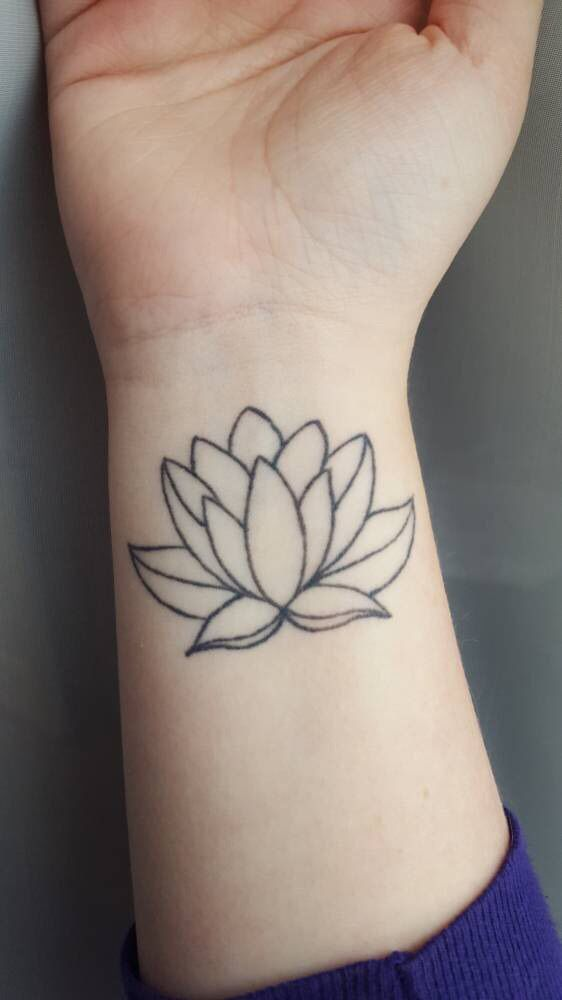 """Lotus flower tattoo on Emily's right wrist: """"Grows out of dark, muddy water and opens its petals to the sunshine. Symbol of maturity and enlightenment."""""""