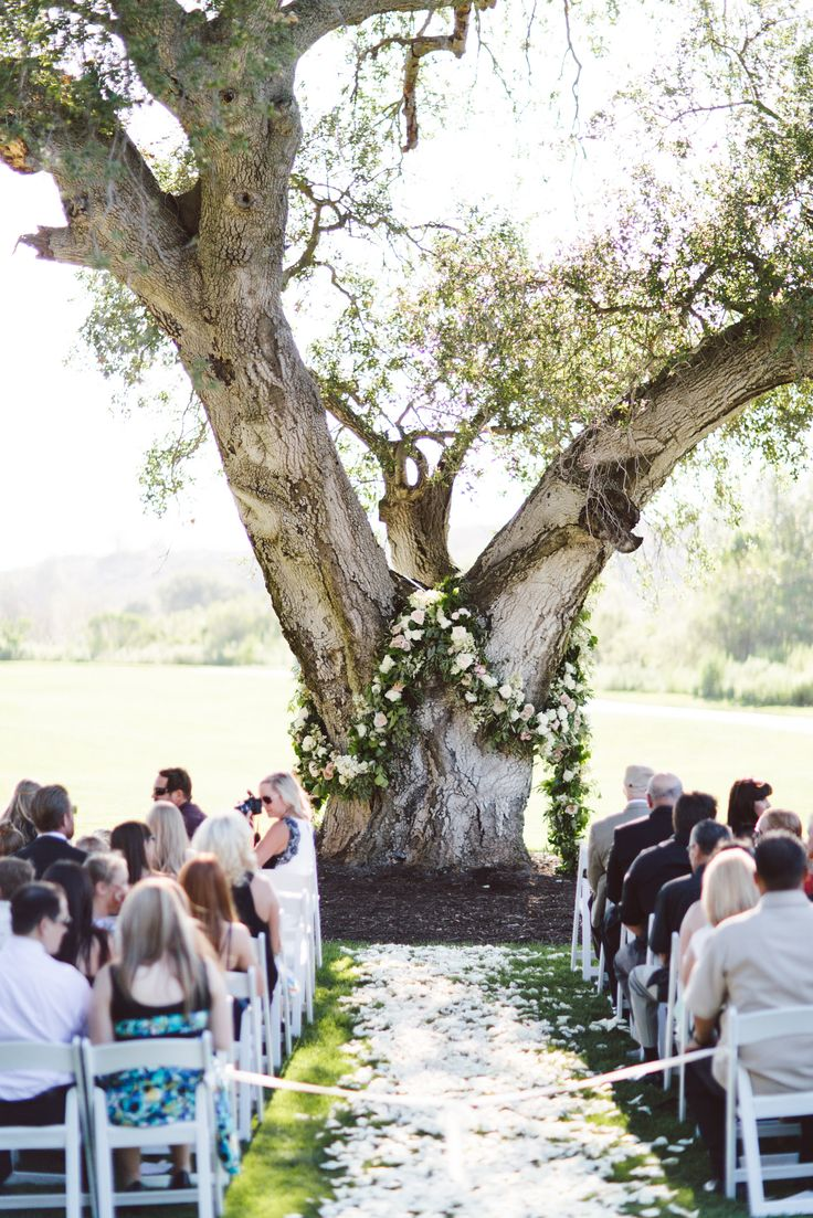 Old oak tree ceremony with floral garland