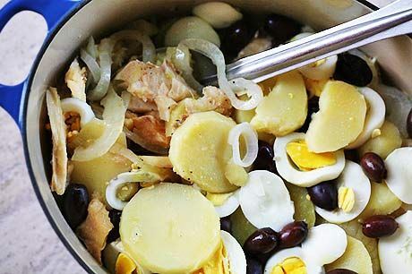 Traditional bacalhau recipe, a Portuguese salt cod stew made with salt cod, potatoes, onions, hard boiled eggs, olives, and lots of olive oil.