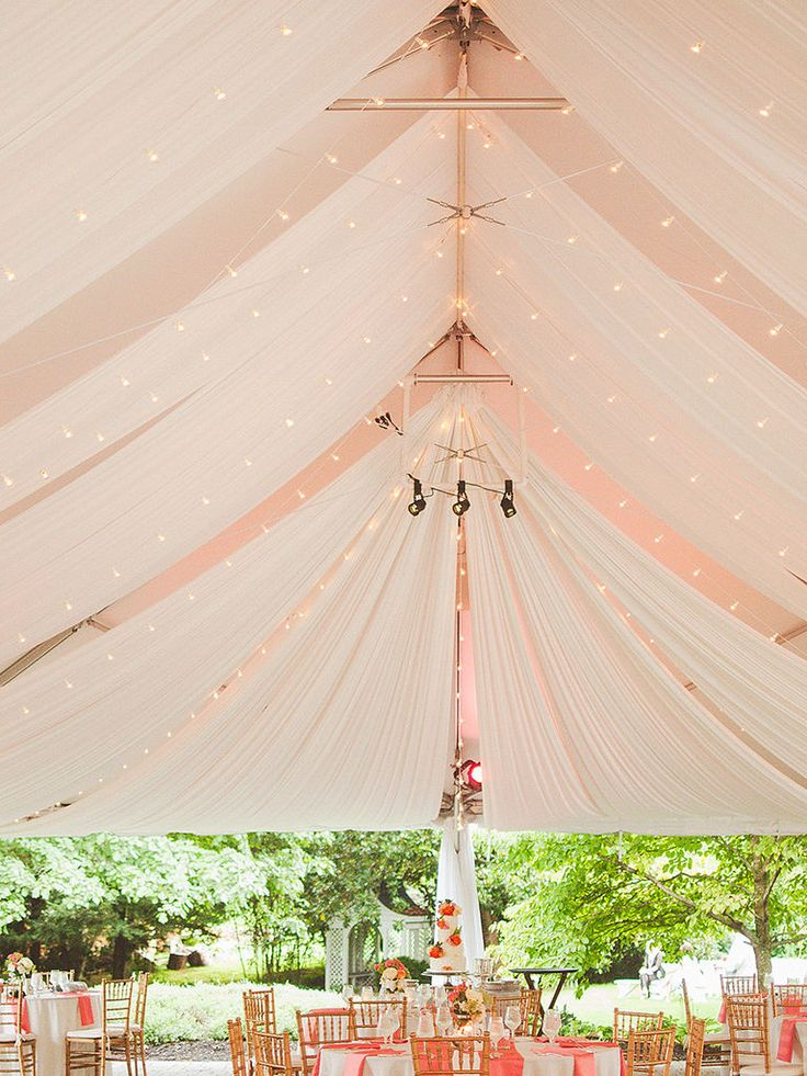 Outdoor wedding tent with draped fabric and string lights