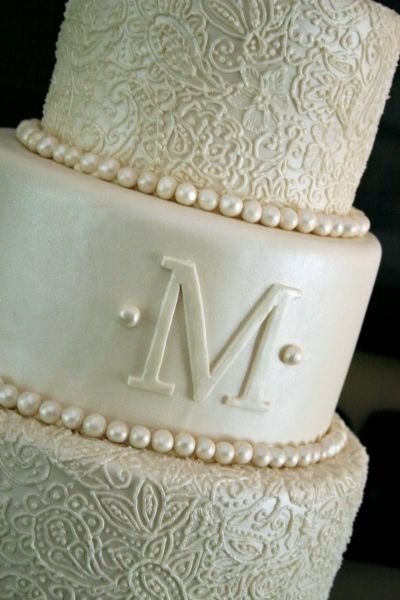 "Monogram wedding cake...I like the middle tier ""M"" mine ""N"" with the pearls then have my roses for the bottom two"