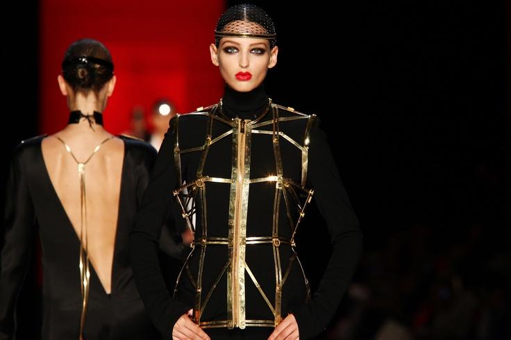Collection Haute Couture automne-hiver 2012-13  Modèle n°16  Muscadin : Tailleur Pantalon en crêpe noir. Gilet-cage à rivets en règles coulissantes en laiton doré.  www.jeanpaulgaultier.com #JPGaultier #PFW #couture