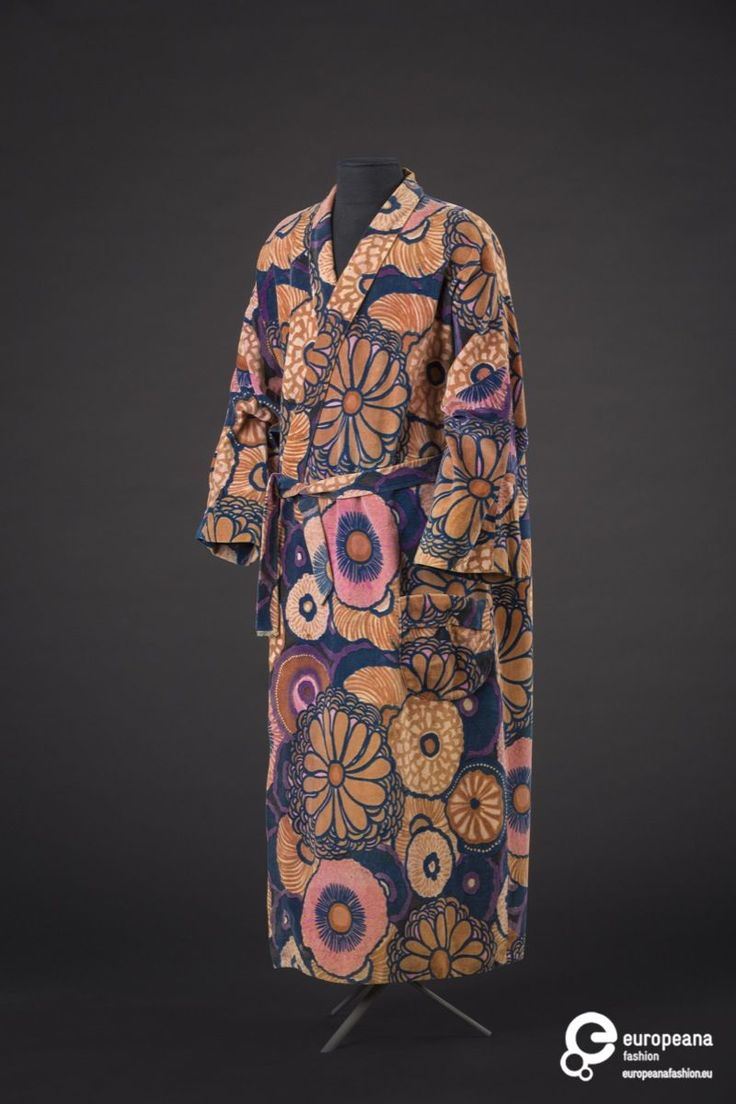 The housecoat for man is made of cotton velvet, printed with a floral pattern in multiple colours. It was designed by Paul Poiret in 1923, and made using the fabric produced by the Atelier Martine, the designer's atelier dedicated to interior and textile design. Lange kamermantel in effen fluweel met bloemenprint in roos, blauw, beige en paars van Maison Martine