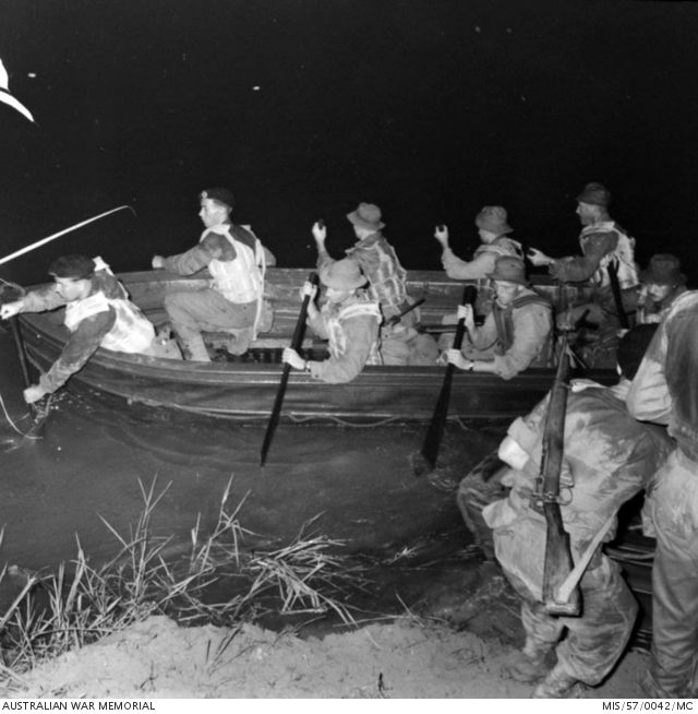 A mixed group of unidentified soldiers, some from 2nd Battalion, The Royal Australian Regiment (2RAR), prepare to make a night river crossing in canvas and timber folding boats (folboats) as they set out on a patrol in pursuit of Communist terrorists in the jungle of Northern Malaya. The soldier (right) preparing to board the second boat is armed with a Number 5, Short Magazine Lee Enfield (SMLE), jungle carbine. April 1957