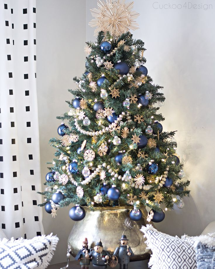 small Christmas tree with blue ornaments, silver garland and German straw stars