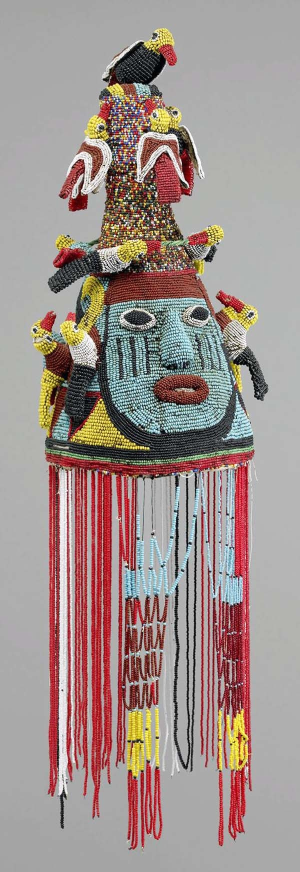 Africa | Royal headdress.  Yoruba people.  20th century. Fiber and glass beads | Beaded items have long been associated with royalty among the Yoruba. Cone-like crowns like this one are primary symbols of a king's authority. When wearing it, a king becomes connected to royal ancestors, thereby strengthening his authority.  Since it is prohibited for people to gaze directly at the king's head, a veil is included to conceal him.