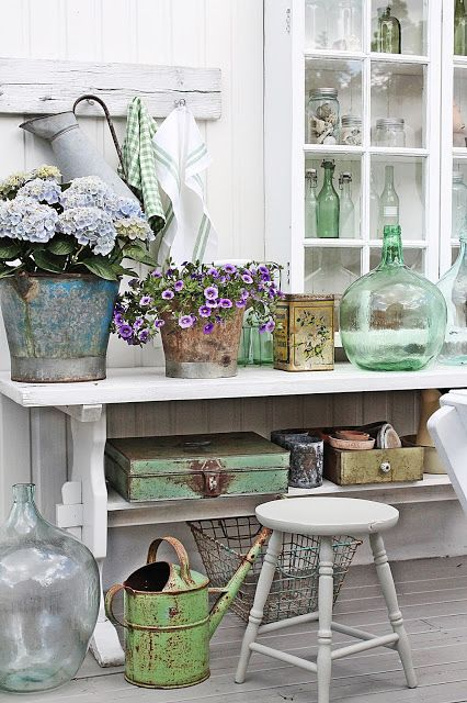 Pretty blue and green decor.  Love the old containers and the distressed white wood wall hook and the pitcher hanging from it.
