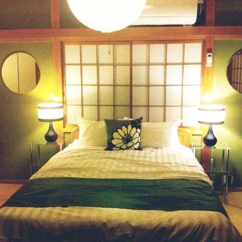 日本家屋の佇まいを生かした和レトロMIX。抹茶色の土壁に合わせた濃緑のベッドランナー、障子の格子柄を中心に、円鏡やランプなどを左右対象に仕立てた上級インテリアです。