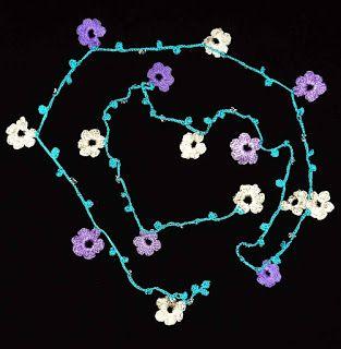 Cordón de flores tejido a crochet en colores lila y blanco ostra decorado con mostacillas transparentes