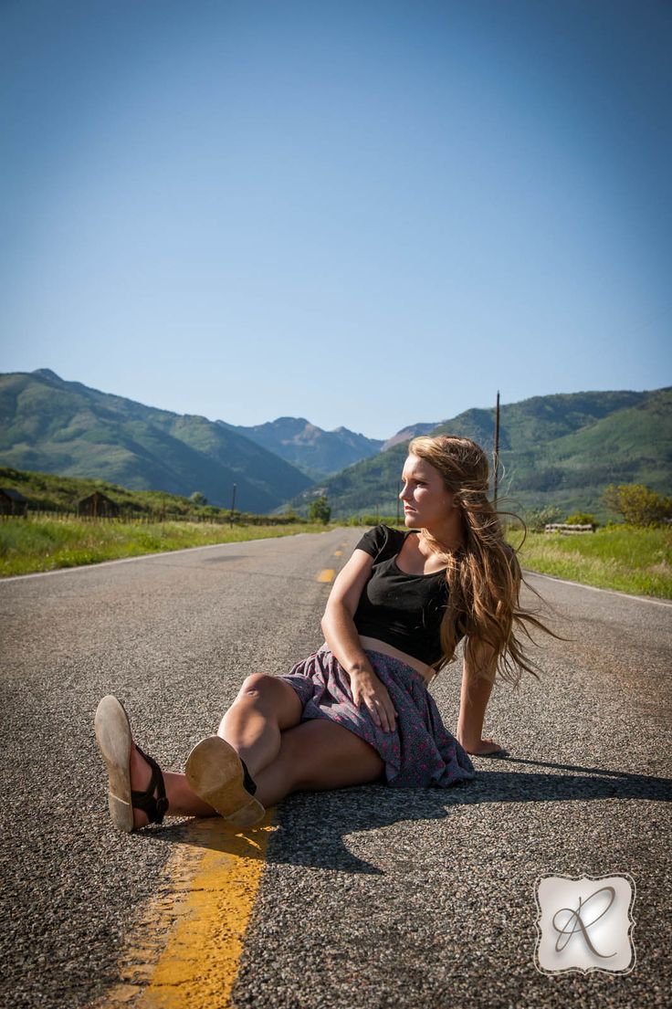 creative outdoor senior pictures, sitting in the road with mountains in background