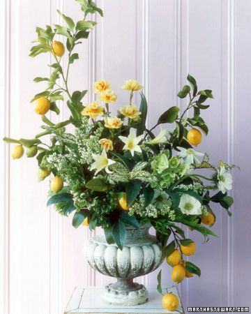 Bright yellow lemons add a pop of color to this arrangement of jonquils, amaryllis, anemones, lilacs, and hellebore