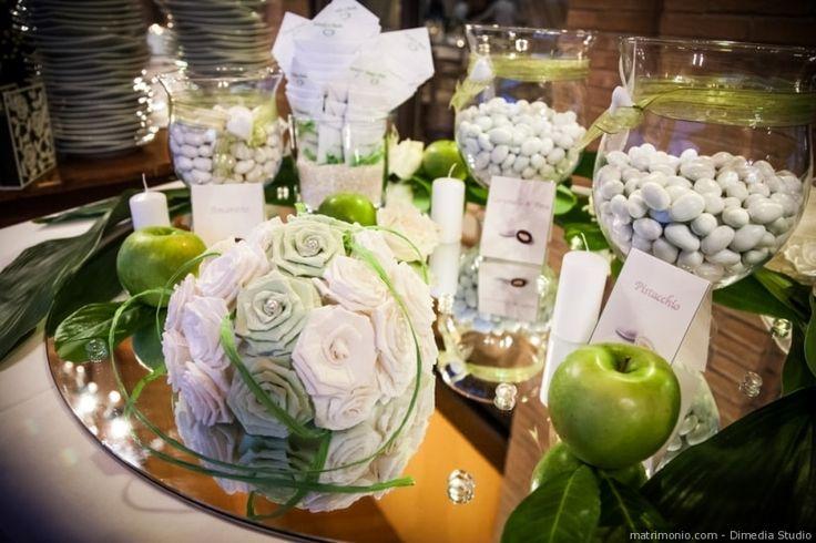 Confettata di nozze con il colore verde Greenery. Decorazione del tavolo con specchi, mela verde e vasi di cristallo con confetti