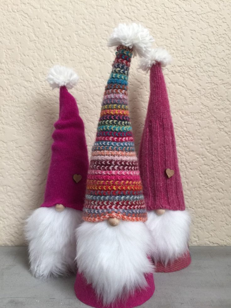 These whimsical Tomten have been lovingly created from repurposed wool and felt. Their hats are hand stitched with embroidery floss from a colorful striped 100% Scottish wool scarf and hot pink cashmere and thick raspberry able cashmere cable knit sweaters. Each hat is adorned with a tiny wooden heart. Their beards are soft, bright white faux fur. They sport color coordinated cashmere-like coats covering their hollow bodies. And their little wooden noses peek out from under their woolen…