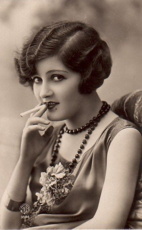 This is a picture of a flapper. As you can see, she is smoking, which was a new thing and an odd thing for a women to do. She also has the classic flapper hair, and a dress which shows a little more skin.