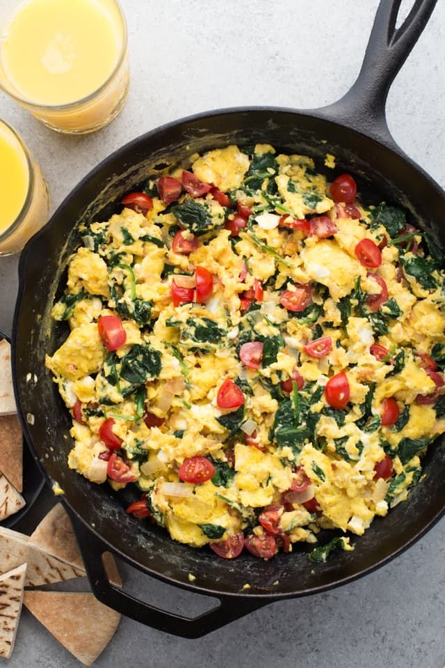 Scrambles are one-pan wonders. Rummage through your fridge, see what needs to be used up, add eggs, and a satisfying breakfast (or dinner) is ready in mere minutes. In this Greek-inspired version, baby spinach, onions, feta cheese, and cherry tomatoes are sautéed with soft-scrambled eggs. Toast up some pita bread (or make pita chips!) and breakfast is ready!