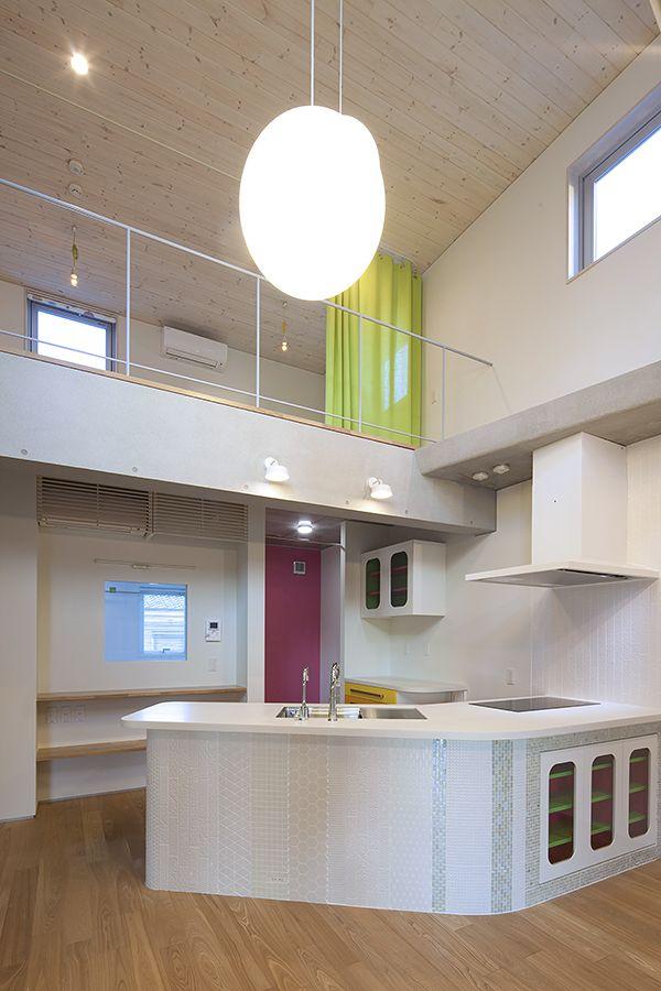 リビングに対してブーメラン型のキッチン。側面はモザイクタイル。