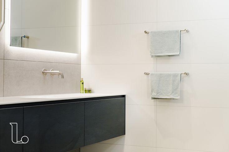 Een zwart badkamermeubel met RVS accessoires en een spiegel met licht. Bekijk deze en meer badkamers bij Laurens Badkamers.
