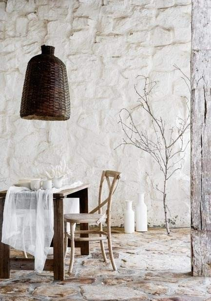 White brick walls, wicker lamp, plant and white bottles. Lovely mix of elements.