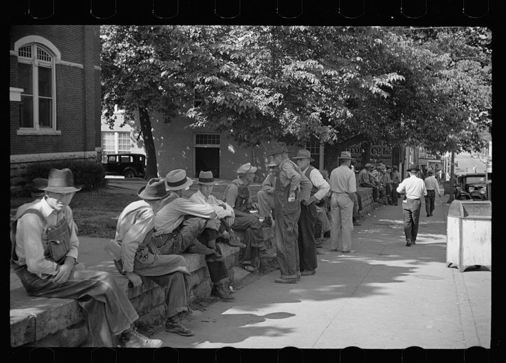 "June 1936.  Loafers' wall, at courthouse, Batesville, Arkansas. Here from sun up until well into the night these fellows, young and old, ""set"". Once a few years ago a political situation was created when an attempt was made to remove the wall. It stays. When asked what they do there all day, one old fellow replied: ""W-all we all just a 'set'; sometimes a few of 'em get up and move about to 'tother side when the sun gets too strong, the rest just 'sets'."""