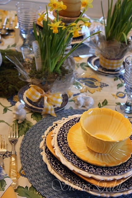 fanciful white decoration plates, layered with navy floral, and popped with an architecturally floral inspired yellow plate and bowl. Spring.