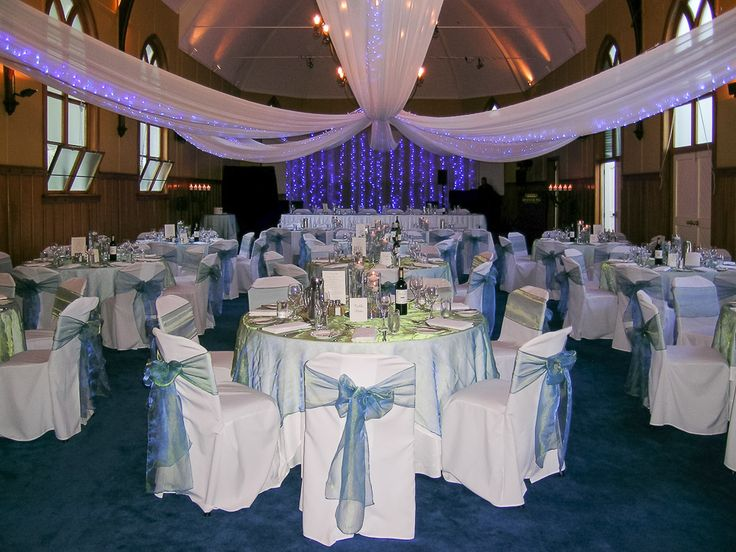 Emma & Ben - October 2014 - Mission Estate Winery - Blue & Green shot organza overlays, trio of glass vases with Blue Delphinium and floating candles, blue sashes adn dramatic blue canopy and backdrop lighting feature.