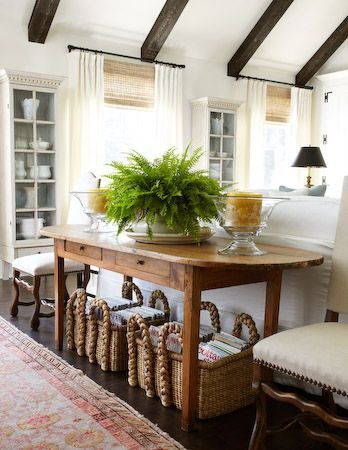 Bright white walls, wood beams, vintage rustic wood console, woven rectangular seagrass baskets under console, vintage faded Persian runner in front of console, black lampshade, white sofa, Ivory linen drapes over woven Romans, fern, vintage chairs: