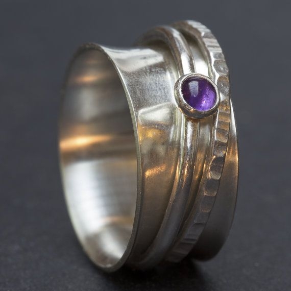 This is a wide band sterling silver spinner ring with 2 spinning rings, one of which is set with an amethyst cabochon stone. The base ring is