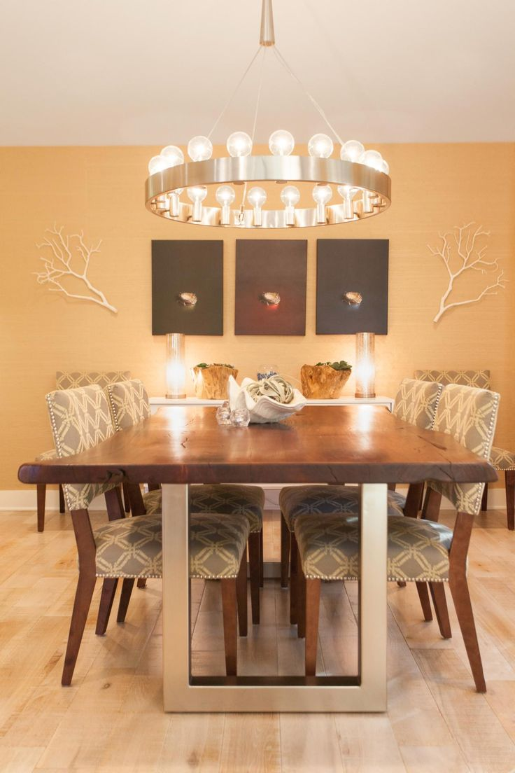 This contemporary dining room features a neutral palette of gray and gold. The live edge walnut table adds a natural element to the space, yet its stainless steel legs maintain a contemporary feel. The gray and tan print of the chairs provides a welcome graphic pop.