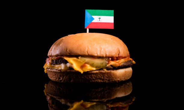 equatorial guinea flag on top of hamburger isolated on black