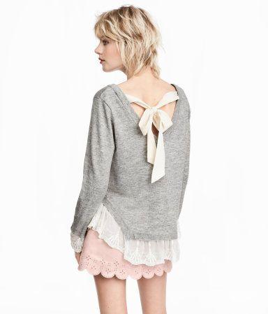 Pullover aus weichem Feinstrick. Der Pullover hat einen tiefen V-Ausschnitt im Rücken mit Bändchen im Nacken. Lange, asymmetrische Ärmel mit Spitzenborte.
