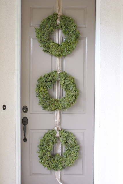 three small wreaths, I would tie together with wide white, silver or apple green satin ribbon. Wreaths can be any type of greens, I love boxwood