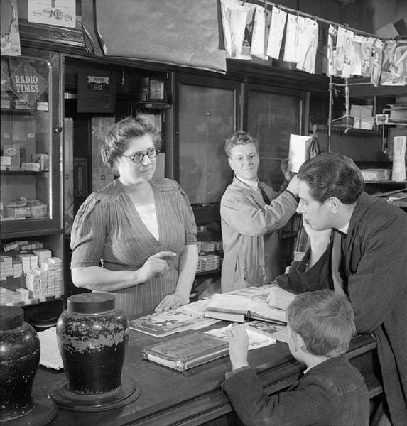 Reverend Joseph Stephens runs through the music for Sunday service with newsagent and church organist Mrs Fry in her shop in Silvertown. A small boy stands next to Rev Stephens as he waits to buy stamps from Mr Fry, who is working behind the counter with his wife.