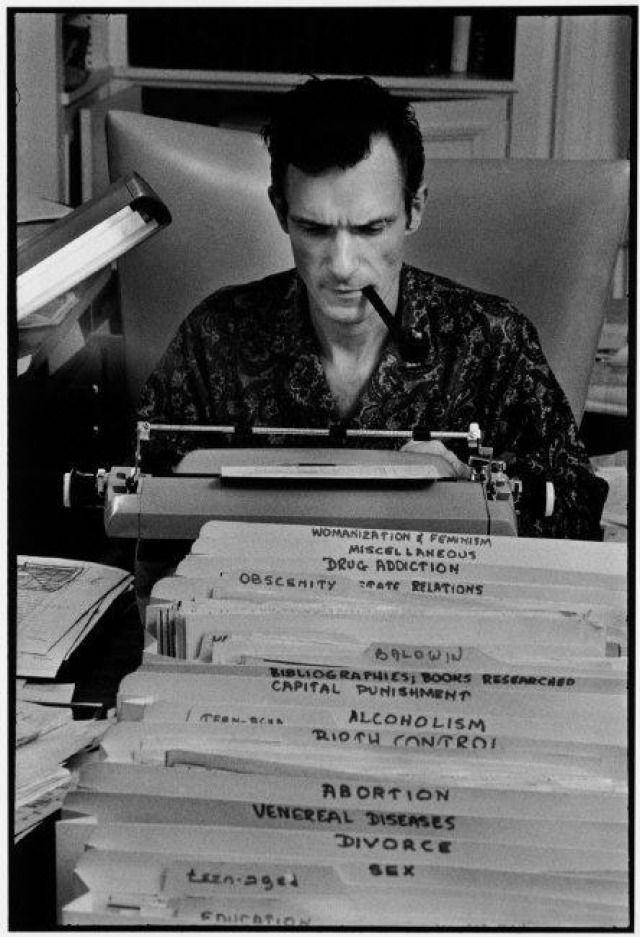 Hugh Hefner, Playboy founder, typing at his desk in his mansion.