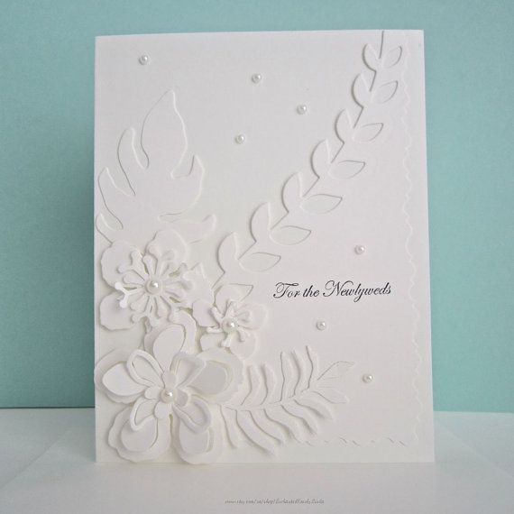 White on white floral wedding card embellished with die cut flowers, faux pearls. The top layer features a die cut leaf motif with fancy
