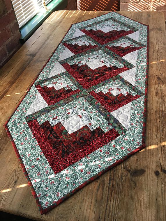 Decorate your holiday table in style this year. Ive stitched together this great holiday table runner. Its of a patchwork style, mostly in reds and greens with the reverse in mostly white. Most of the fabrics have a silver thread running throughout (look at those close up photos), which