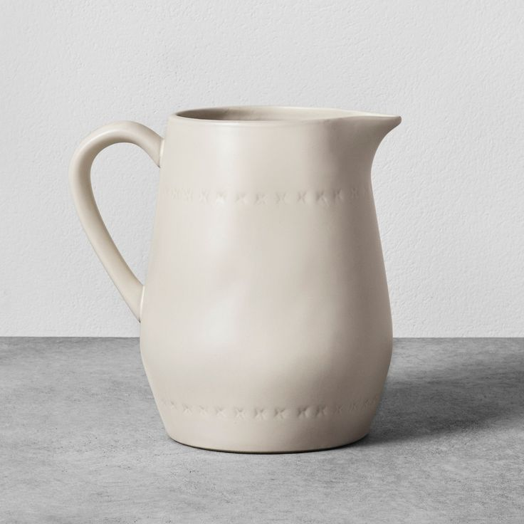 Add a bit of rustic flair to your kitchen drinkware with the Stoneware Pitcher from Hearth & Hand™ with Magnolia. In cream, this simple stone pitcher is ideal for serving cold beverages like iced tea or lemonade to family and friends on a warm Sunday afternoon or as a decorative vase to display a beautiful floral arrangement or house plant. Mix and match with other kitchenware items from the Hearth & Hand with Magnolia collection to create your own custom set.<br><br...