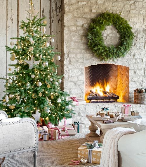 A stone fireplace keeps an elegant Christmas tree toasty on the covered patio of this Arizona home, furnished like a full-fledged living room.   - CountryLiving.com