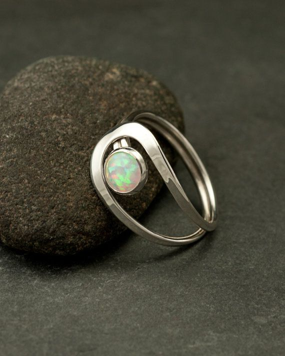 This argentium sterling silver ring is a simple round band that has two curving lines which accentuate a 6mm lab opal gemstone.