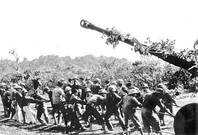 Viet Minh soldiers pulling a howitzer across a hill
