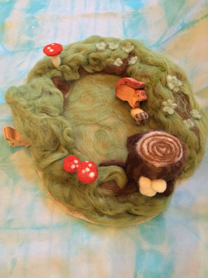 Woodland play mat needle felted with rabbit burrow, acorn, primrose and tree stump