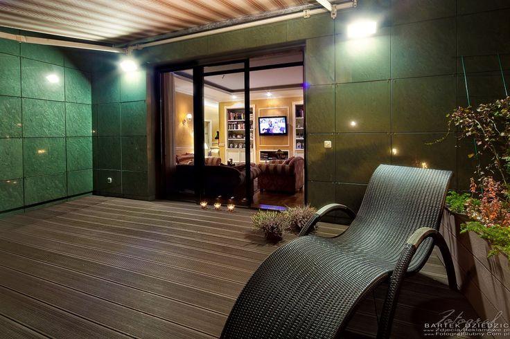 Zdjęcia reklamowe Apartamentu Kraków. Na zdjęciu taras wykończony deskami, leżak. Zdjęcie zostało wykonane w nocy.