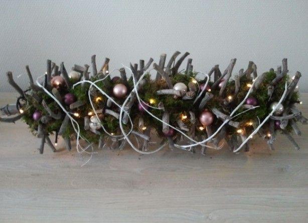 Kersttak. Mos er om gedaan, kerstballetjes er tussen en wat buigzame witte takken erom heen.