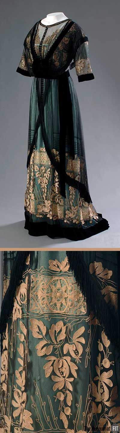 "Dress, Mme. Percy, England, ca. 1910. Aqua silk satin with cream embroidery, net, and black velvet. In the early 20th century, cultivated women regarded pastels and muted shades as refined and ""lady-like."" This aqua silk is muted by a layer of black net and ivory lace. Museum of the Fashion Institute of Technology"