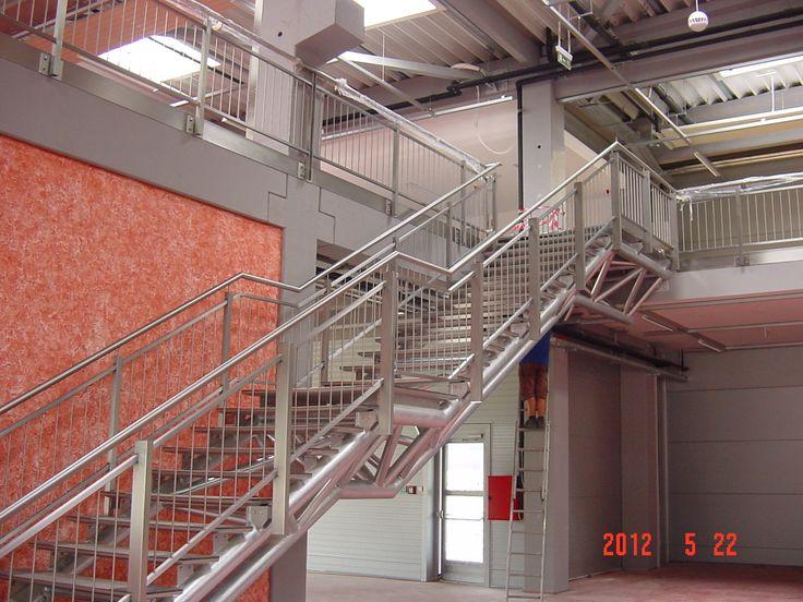 Rozsdamentes korlát zártszelvény oszlopokkal, cső kapaszkodóval és függőleges kiosztású korlátmezővel, szálcsiszolt felülettel. Robosztus hatású, masszív kialakítású szerkezet, elsősorban ipari épületek nagy tereibe ajánljuk.