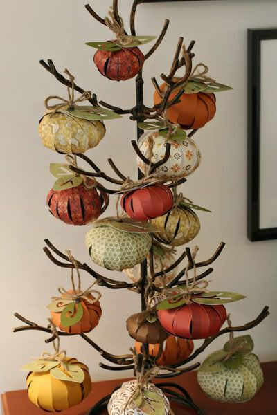 Paper Pumpkin Tree...cut strips of paper from scrapbook papers with fall tones. Punch a hole into the end of each paper strip. Connect them with a metal brad.Then attach a brad to the top add leaves and a little piece of ribbon or string. Too cute!
