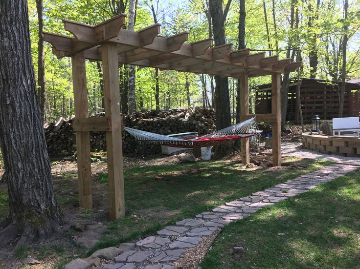 DIY pergola/hammock stand. Built out of cedar tone treated lumbar. Legs are 6*6 and uppers are double 2*8's for strength. Plan to build a couple swings to interchange with the hammock.  A perfect place to relax with the fur babies and my husband.