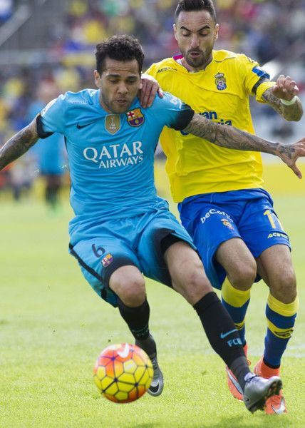 Barcelona's Brazilian defender Dani Alves (L) vies with Las Palmas' midfielder Momo during the Spanish league football match UD Las Palmas vs FC Barcelona at the Gran Canaria stadium in Las Palmas de Gran Canaria on February 20, 2016.