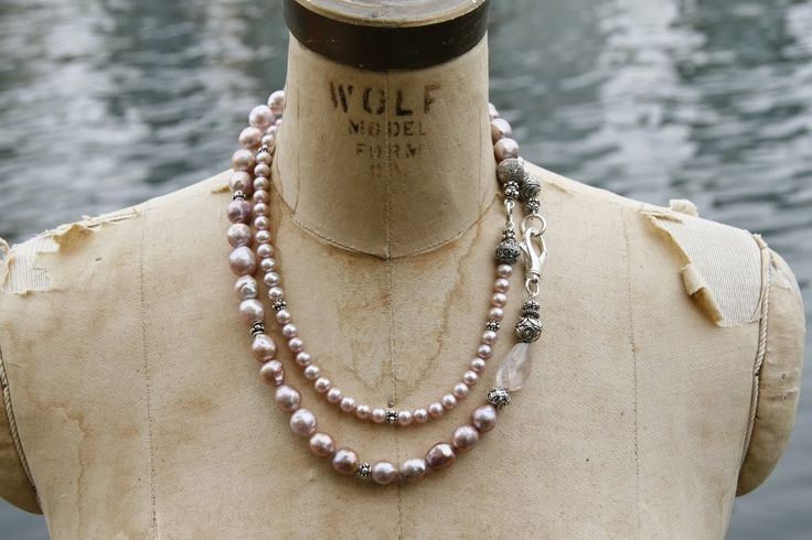 A long rope of pink pearls worn short. The pearls are mixed with sterling silver beads, a rose quartz stone, and a decorative silver lobster clasp.